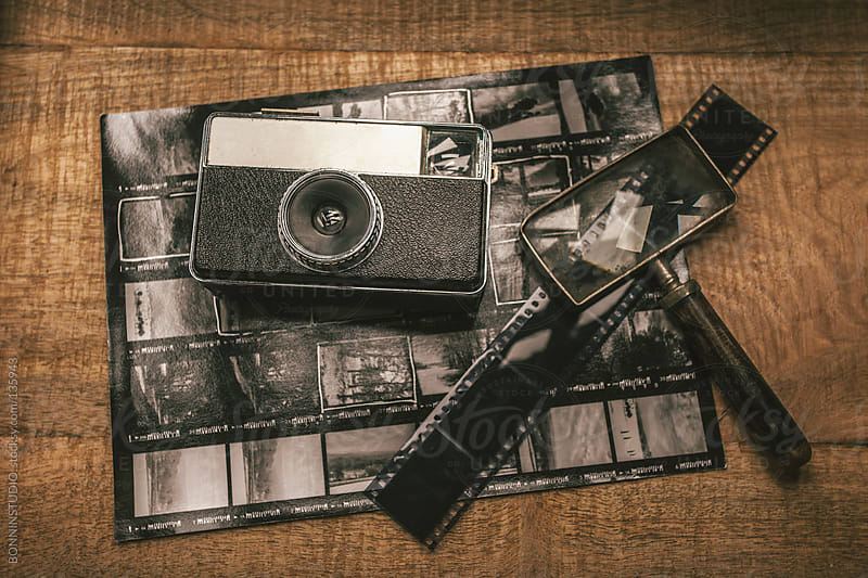 Old analog camera, film, magnifying glass and contact sheet over wooden table. by BONNINSTUDIO for Stocksy United