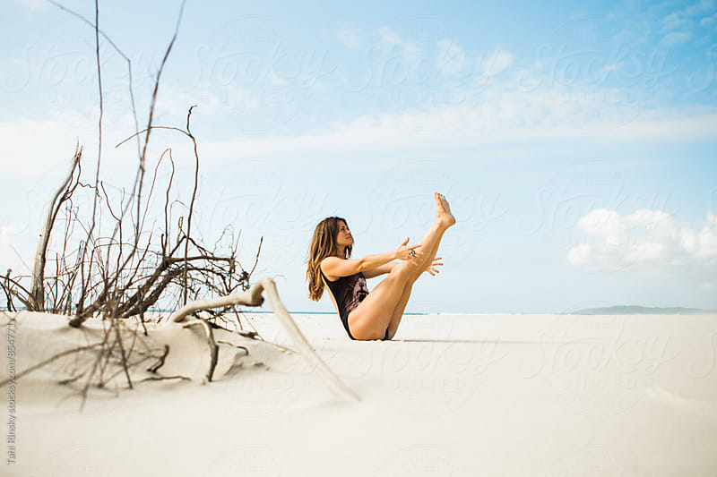 women doing yoga on empty beach  by Tahl Rinsky for Stocksy United