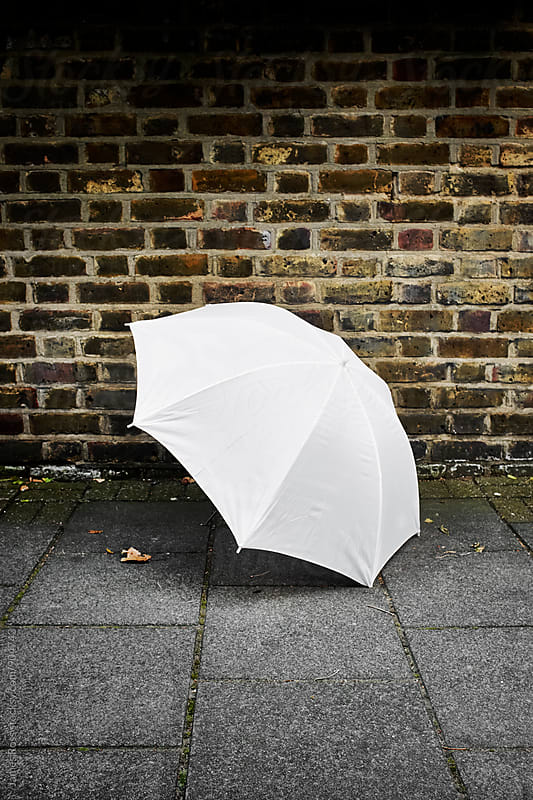 A white umbrella by a brick wall by James Ross for Stocksy United