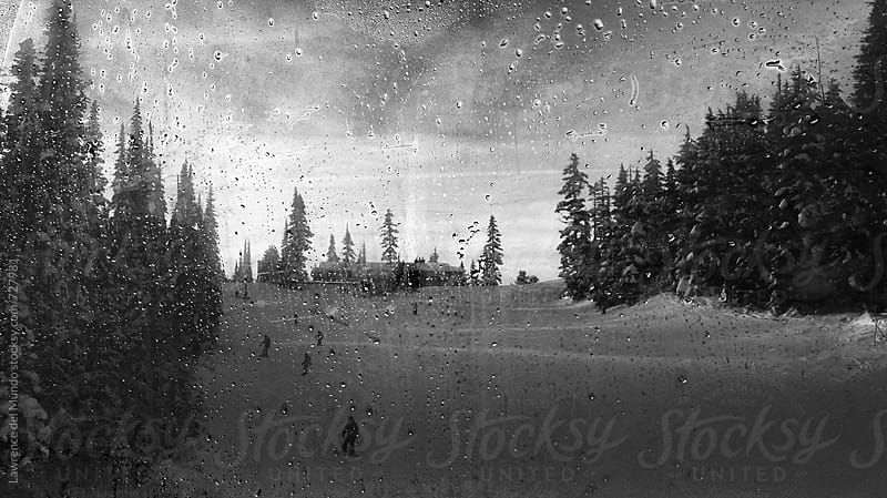 Gloomy mood of a view of skiers going down a slope from inside a cable car by Lawrence del Mundo for Stocksy United