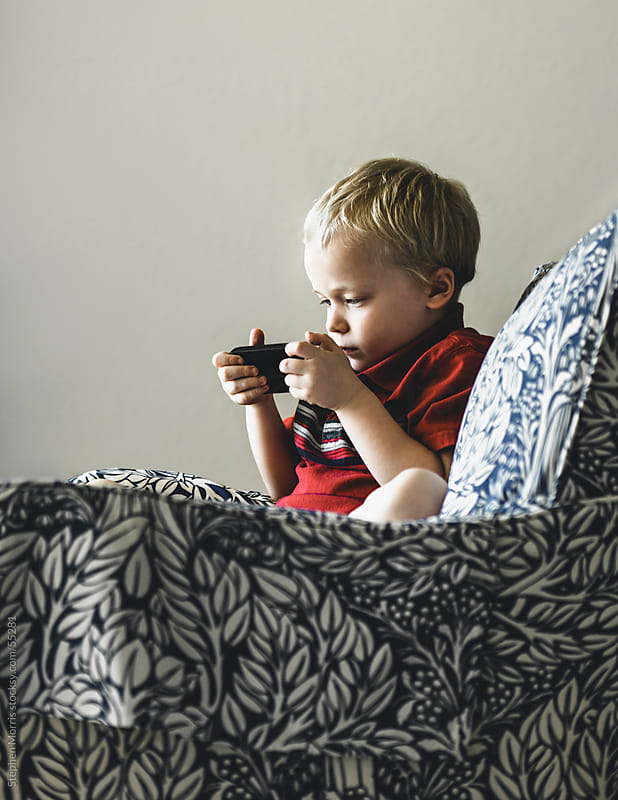 Boy Using a Smart Phone by Stephen Morris for Stocksy United