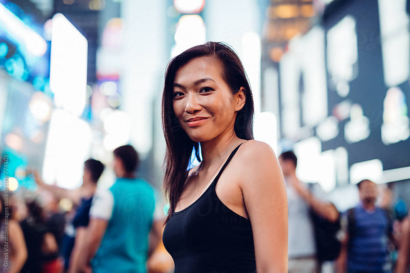Asian Woman looking at camera in Time Square, NYC by Good Vibrations Images for Stocksy United