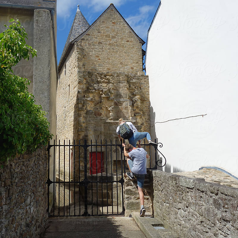 Couple climbing over a gate by Marcel for Stocksy United