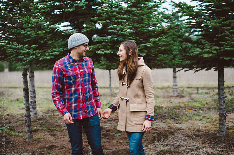 Attractive young couple walking through tree farm together in the winter. by Kate Daigneault for Stocksy United