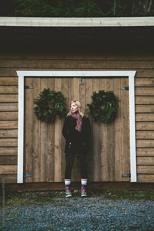 Woman stands in front of barn doors. by Cherish Bryck for Stocksy United