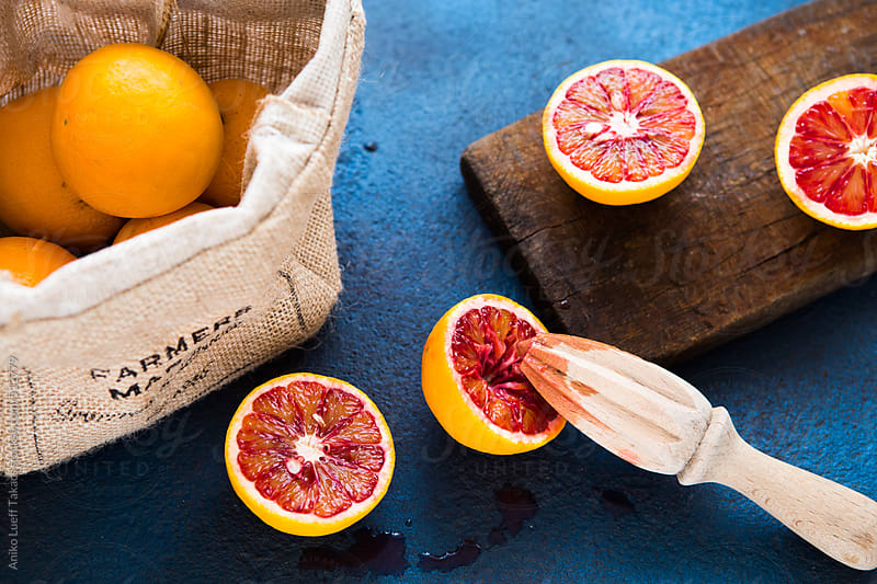 Blood Oranges on a blue board by Aniko Lueff Takacs for Stocksy United