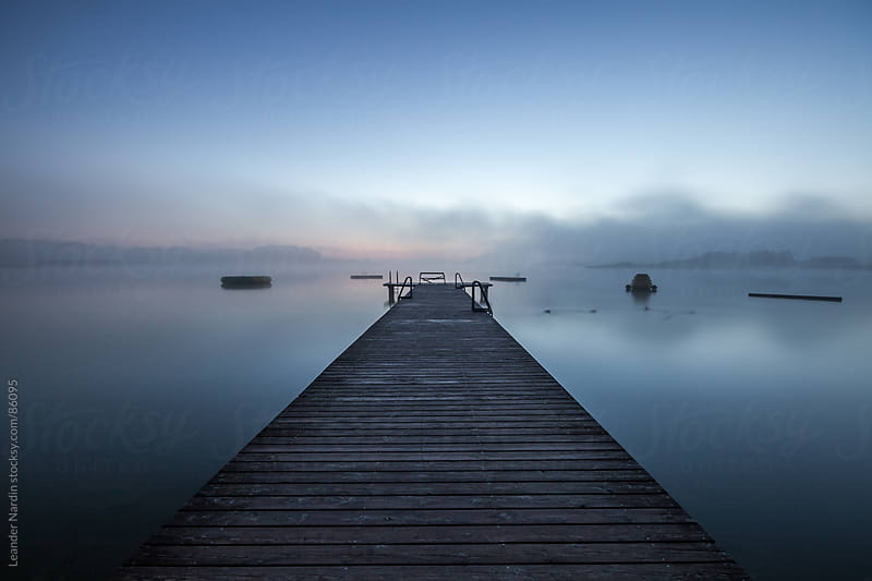 wooden dock on a lake in morning fog at sunrise by Leander Nardin for Stocksy United