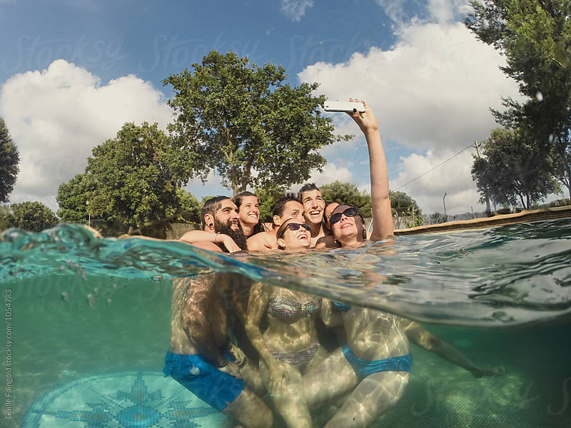 Cheerful friends taking selfie in pool by Guille Faingold for Stocksy United