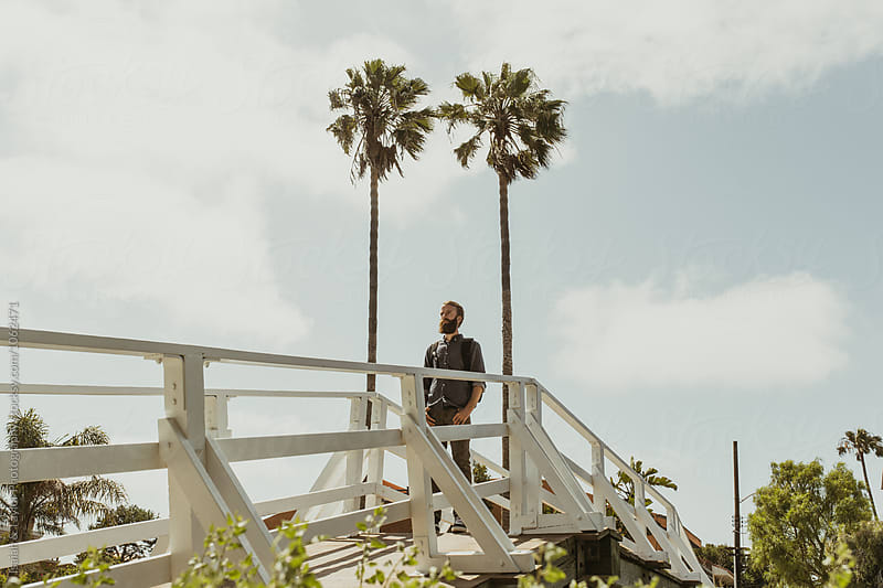 Man on walkway by Isaiah & Taylor Photography for Stocksy United