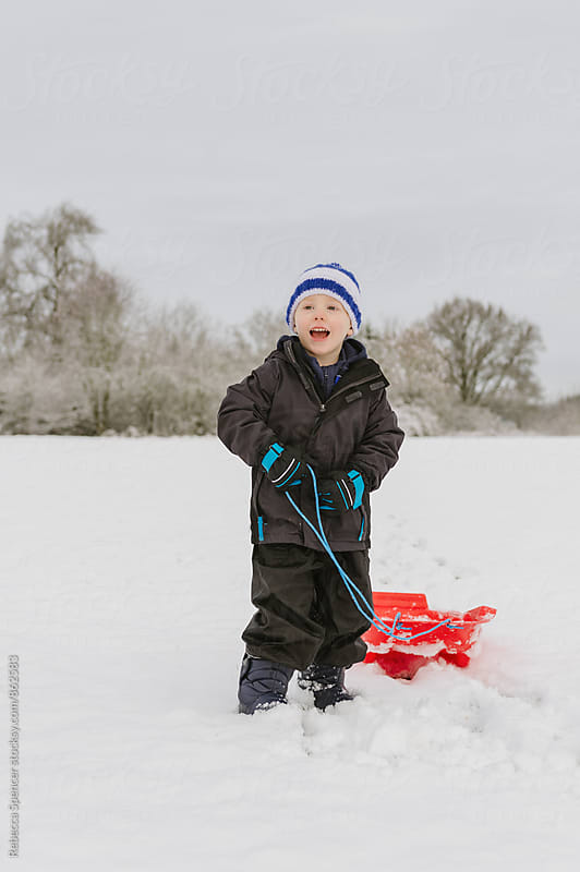 Excited young boy in the snow with sled by Rebecca Spencer for Stocksy United