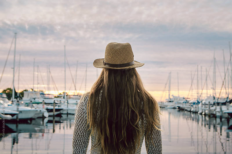 Woman watching sunrise over marina by Stephen Morris for Stocksy United