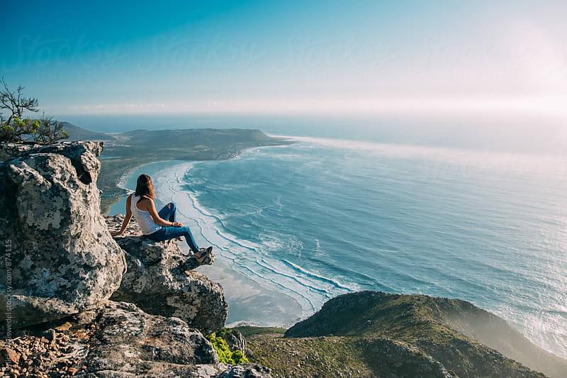 hiker sitting on a rocky outcrop overlooking the ocean by Micky Wiswedel for Stocksy United