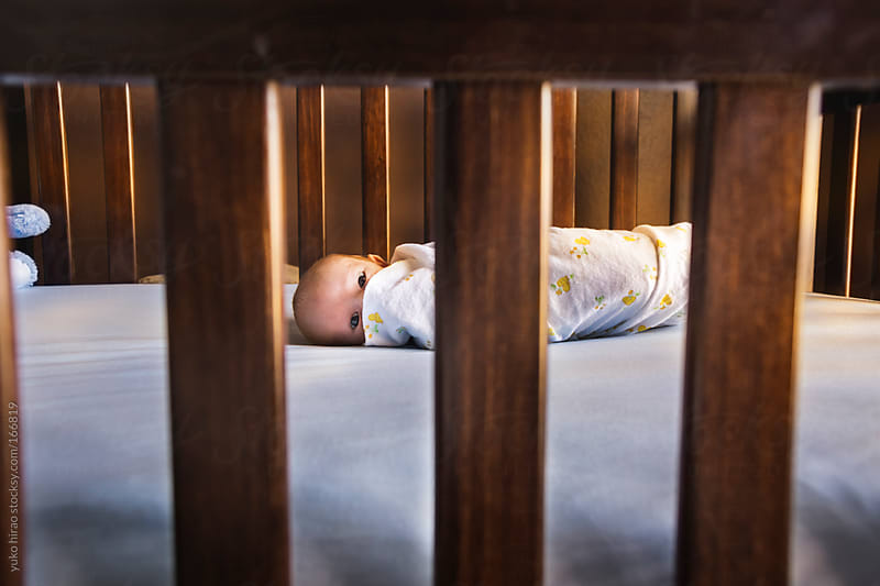 Small newborn baby boy in a crib  by yuko hirao for Stocksy United