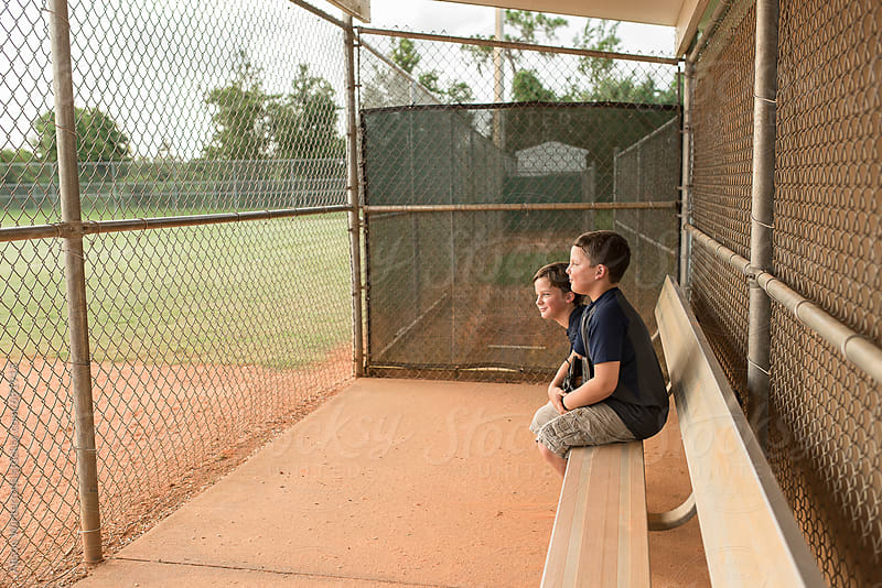 Two Boys Wait In Dugout by Alison Winterroth for Stocksy United