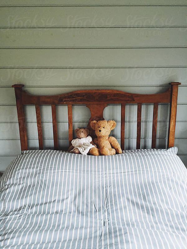 A child's teddy bears on a bed by Helen Rushbrook for Stocksy United