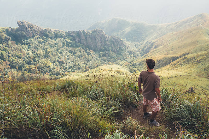 Young man overlooking green mountain landscape from the top of a hill by Alejandro Moreno de Carlos for Stocksy United
