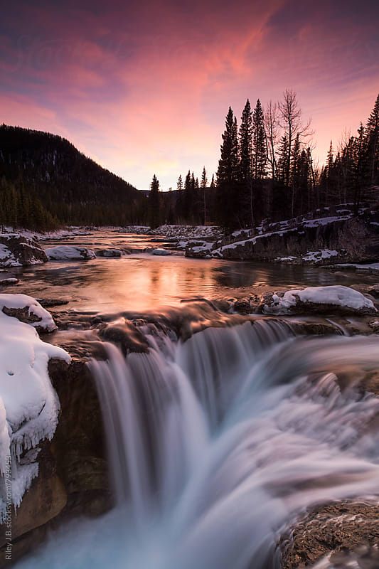 A long exposure of a small water fall at sunset in the winter. by Riley J.B. for Stocksy United