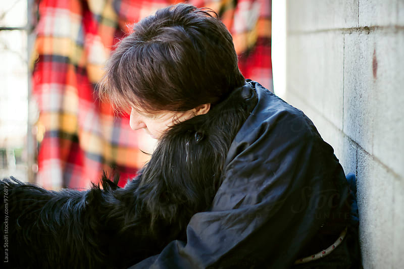 Woman sits down hugging, cuddling and holding in her arms a giant Schnauzer dog by Laura Stolfi for Stocksy United