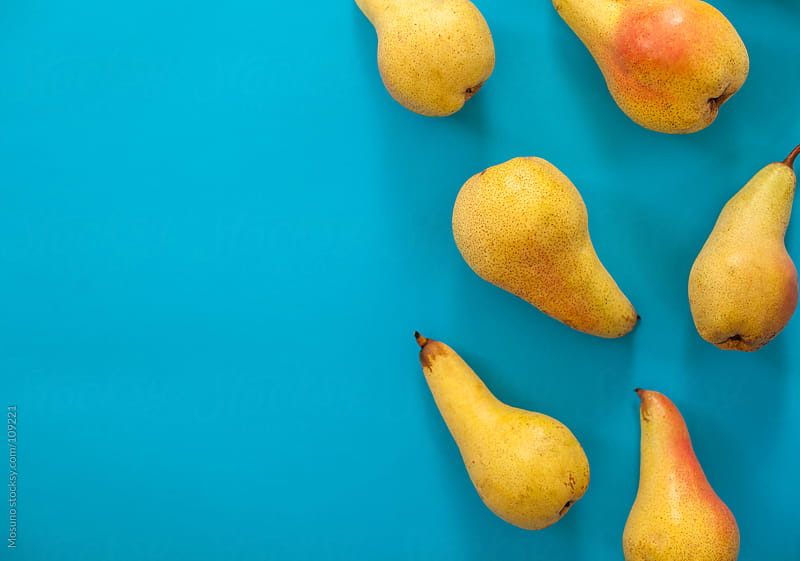 Yellow pears against blue background. by Mosuno for Stocksy United
