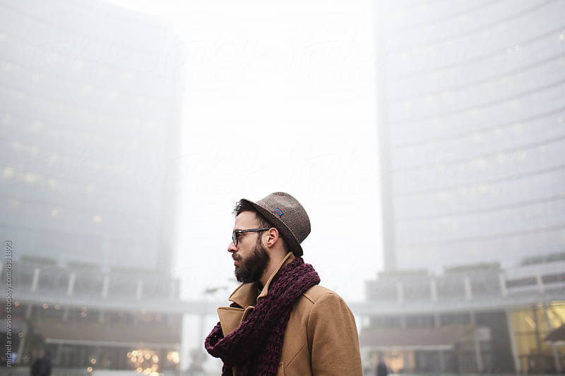 Young man with a beard walking in an urban area by michela ravasio for Stocksy United