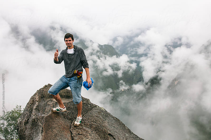 Man with thumb up smiling at camera against of cloudy mountains by Alejandro Moreno de Carlos for Stocksy United