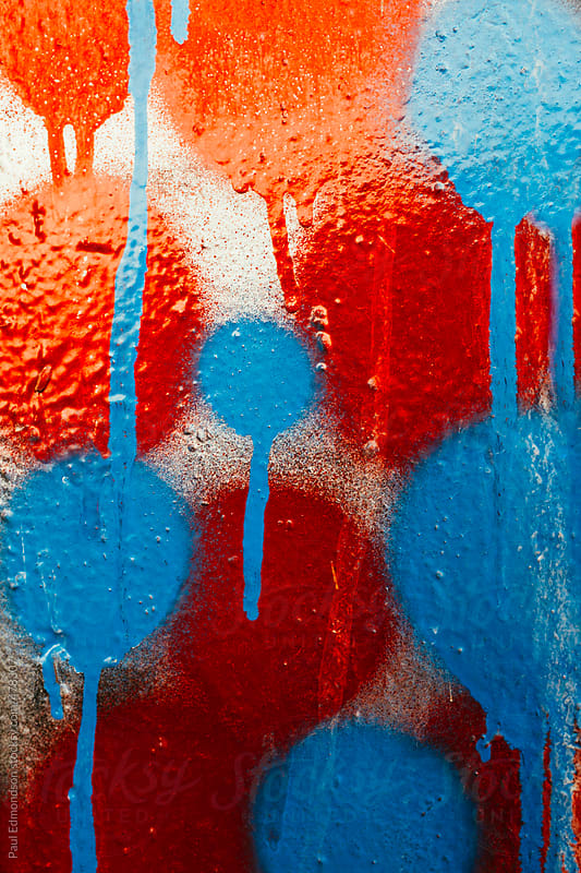 Close up dripping blue and red graffiti paint on wall by Paul Edmondson for Stocksy United
