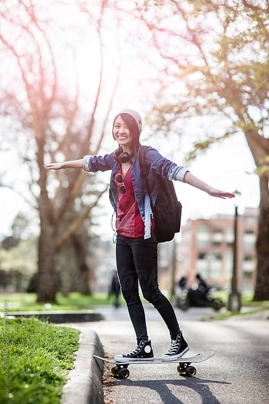 Asian college student riding her skateboard on campus by Suprijono Suharjoto for Stocksy United