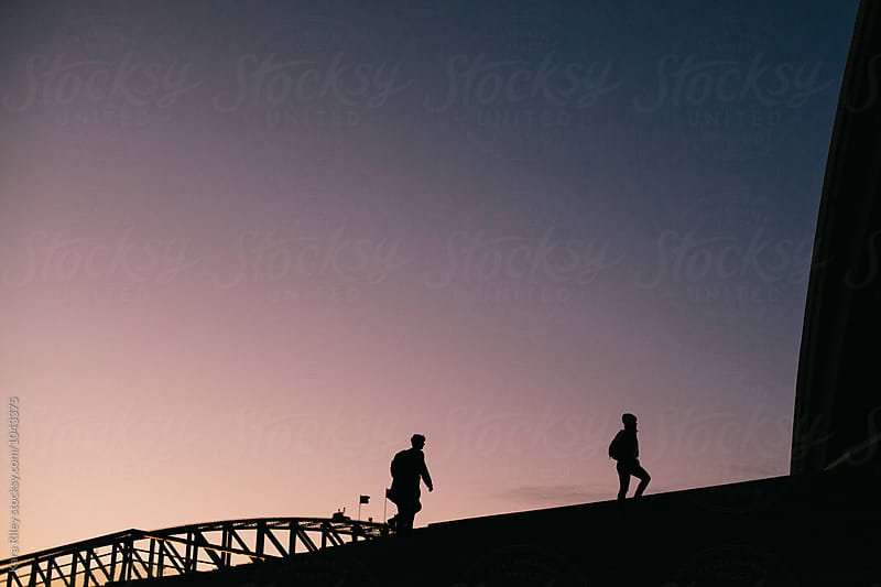 Two people walking up steps in Sydney Harbour by Kara Riley for Stocksy United