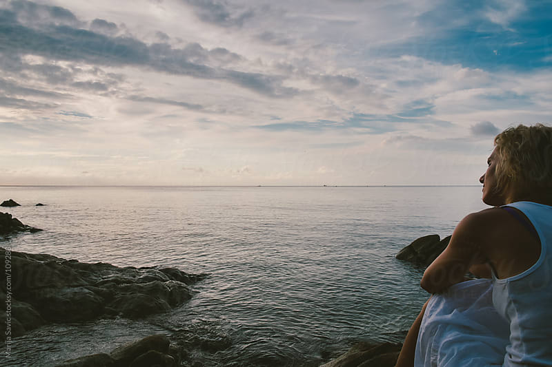 Woman sitting by the ocean. by Marija Savic for Stocksy United