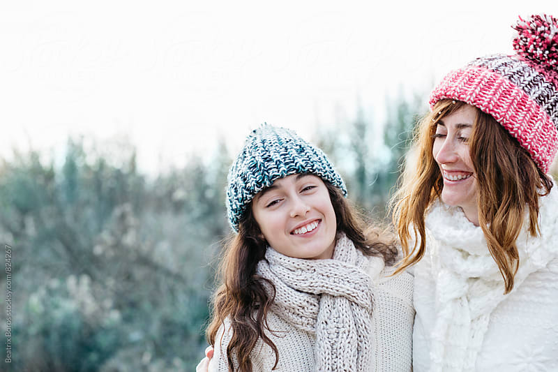 Girl laughing together with her mother in the nature in Winter by Beatrix Boros for Stocksy United