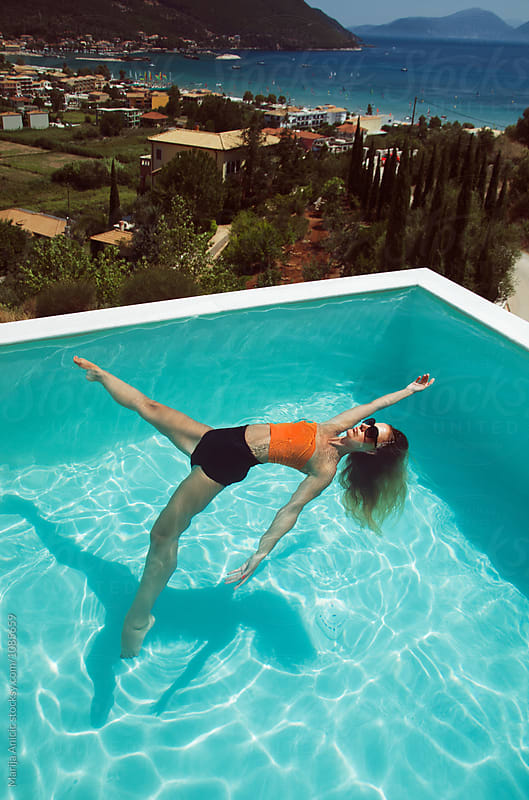 Handsome woman with long hair playing in the pool by Marija Anicic for Stocksy United
