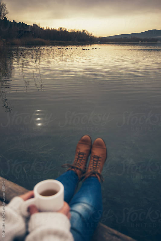 Closeup of legs of a girl with tea cup relaxing at the lakeshore. by BONNINSTUDIO for Stocksy United