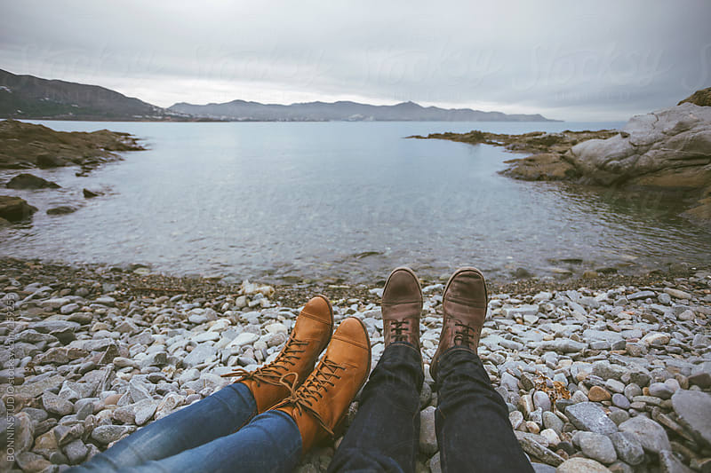 Closeup of legs of couple relaxing at seashore. by BONNINSTUDIO for Stocksy United