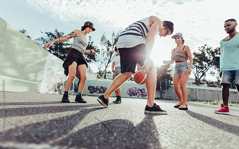 Group of friends playing a game of basketball by Jacob Lund for Stocksy United