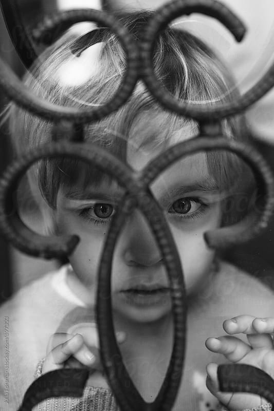 Little girl stares intensely through the curved metal bars on a window.  by Julia Forsman for Stocksy United
