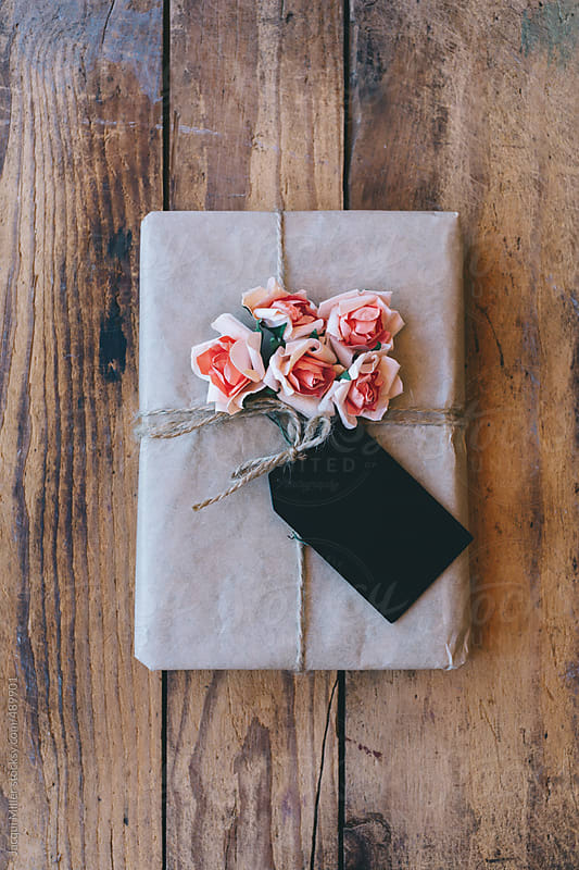 Gift wrapped in brown paper and decorated with paper flowers. Blank tag attached for message. by Jacqui Miller for Stocksy United