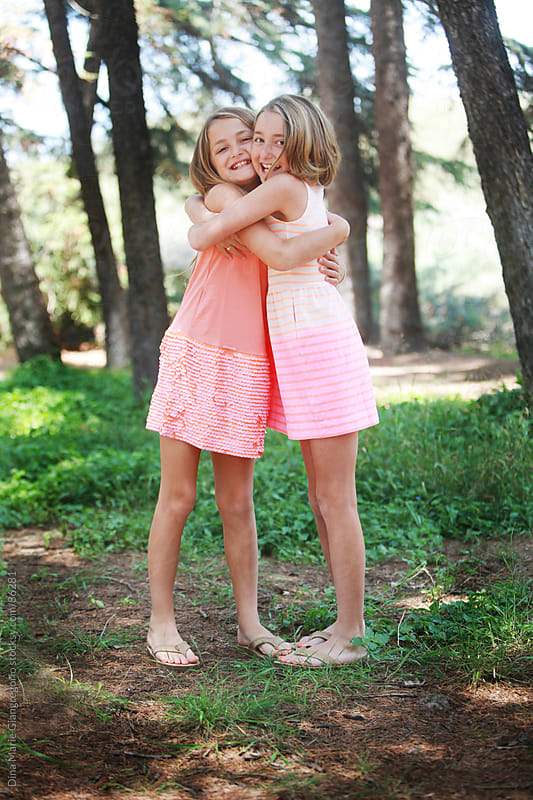 Twin girls in pink dresses hugging In forest by Dina Giangregorio for Stocksy United