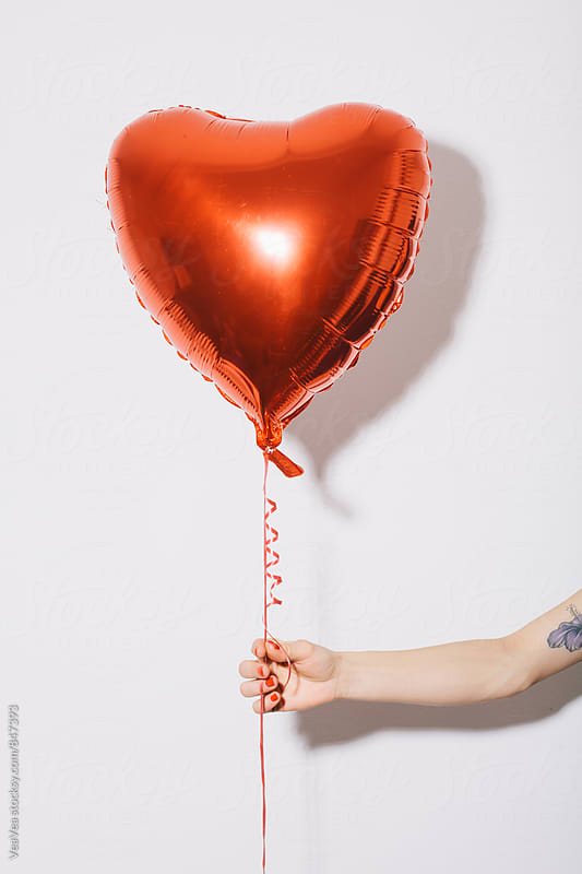 Female hand holding a heart shaped balloon in front of a white wall by Marija Mandic for Stocksy United