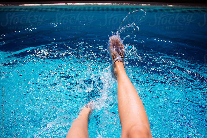 Woman feet splashing in the pool by Susana Ramírez for Stocksy United