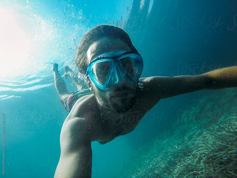 Underwater portrait of young man snorkeling by Marko Milovanović for Stocksy United