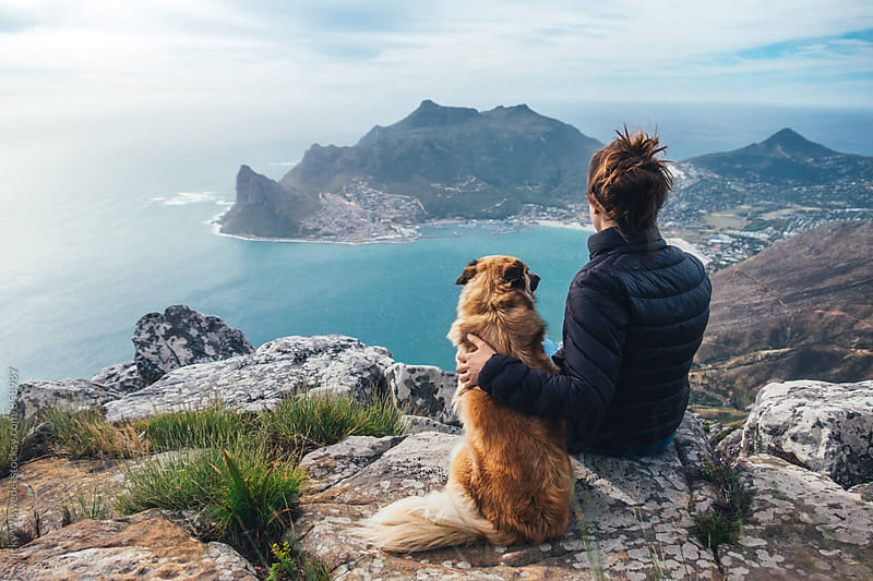 Hiker and pet dog sitting on a rocky mountain summit enjoying a scenic view by Micky Wiswedel for Stocksy United
