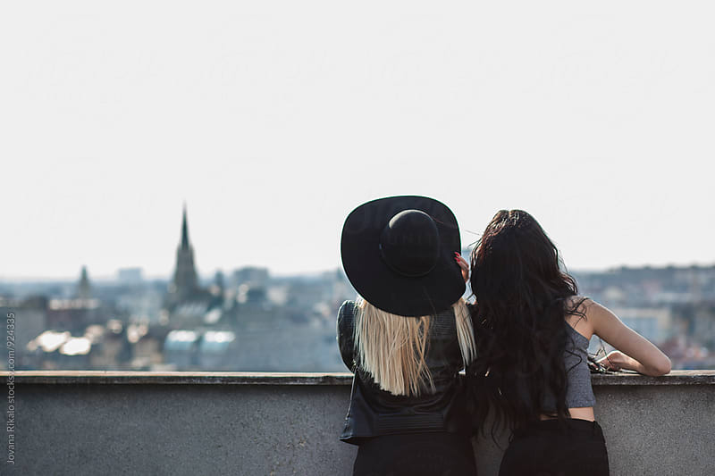 Two female friends on top of the building by Jovana Rikalo for Stocksy United