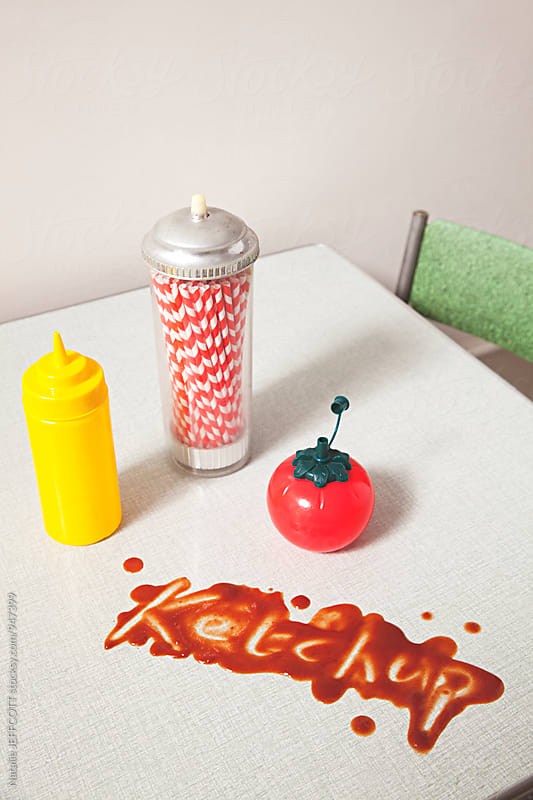 Retro diner scene with tomato ketchup / sauce dispenser with spilt ketchup on table top by Natalie JEFFCOTT for Stocksy United