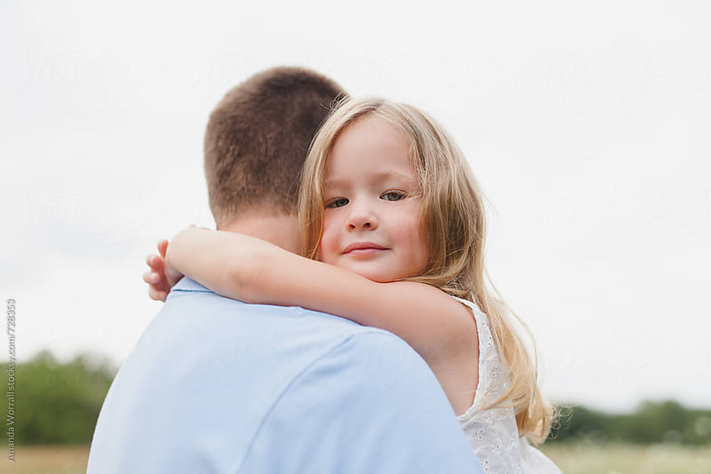 Beautiful young girl looks over father's shoulder, looking at camera by Amanda Worrall for Stocksy United