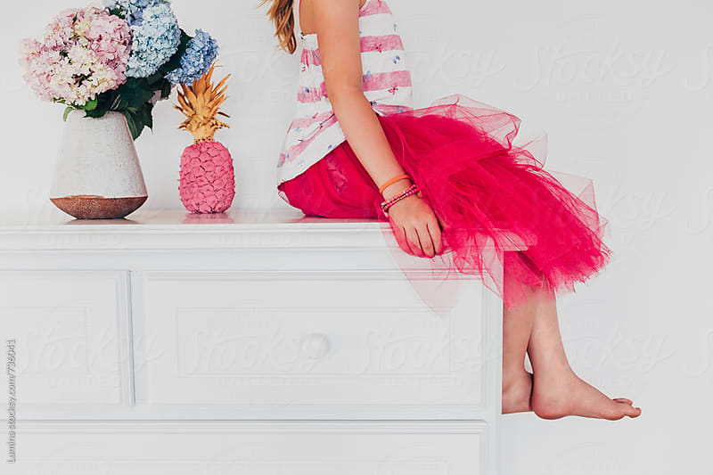 Girl in a Pink Skirt Sitting on a Chest of Drawers by Lumina for Stocksy United