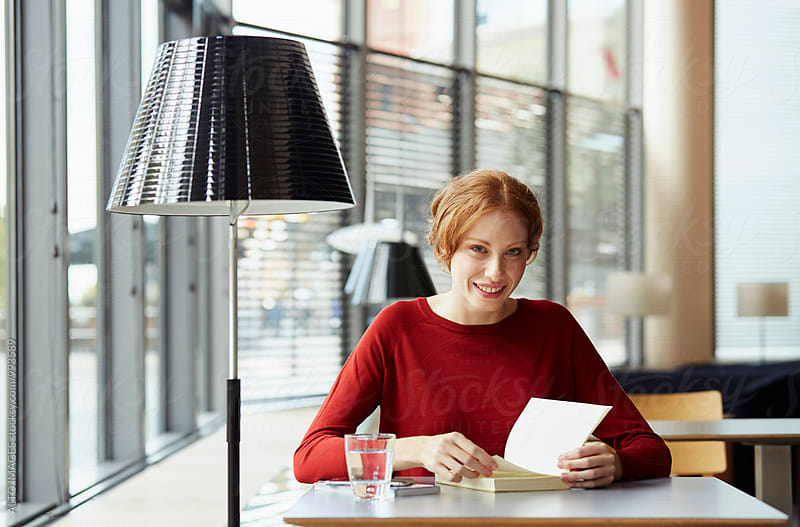 Portrait Of Happy Woman Reading Book In Restaurant by ALTO IMAGES for Stocksy United
