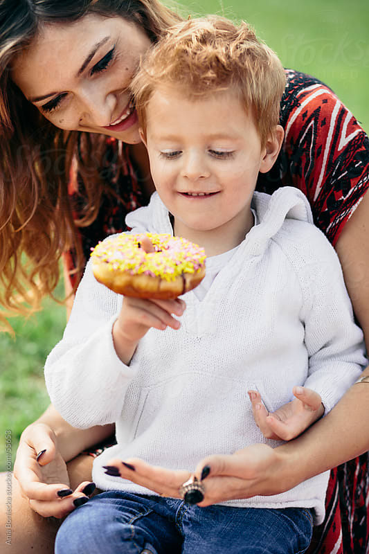 Mother and son at a family picnic, eating a doughnut by Ania Boniecka for Stocksy United