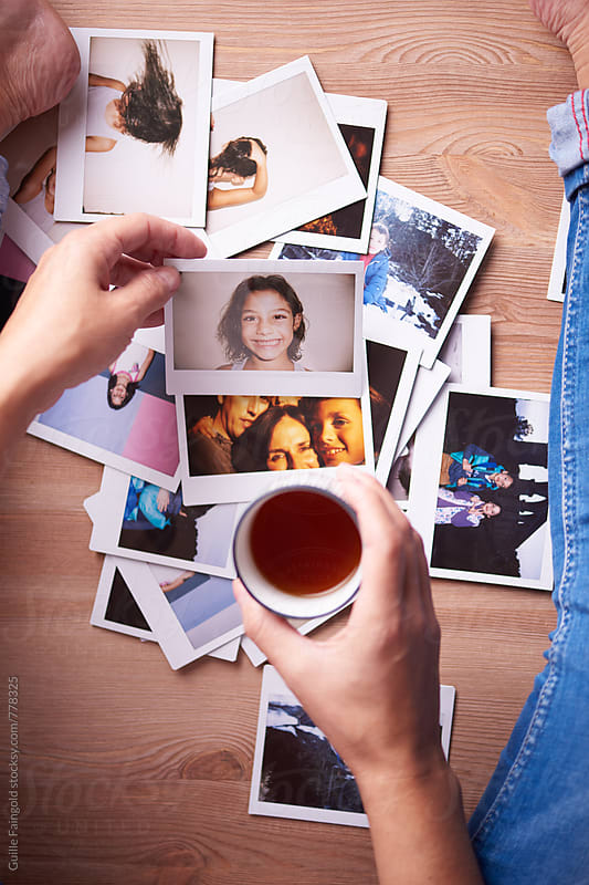 overhead view: woman holding tea cup over bunch of family polaroids by Guille Faingold for Stocksy United