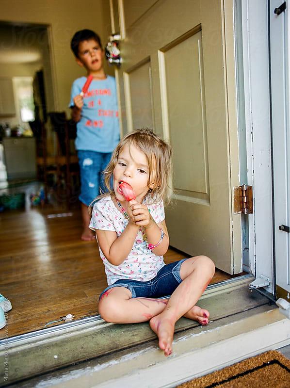 kids eating popsicle in doorway by Maria Manco for Stocksy United