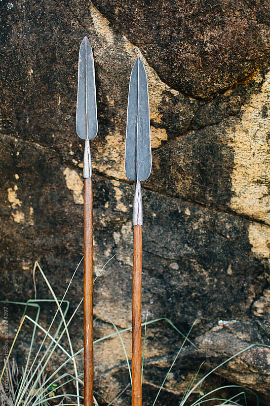 traditional Maasai spears leaning against rock by Cameron Zegers for Stocksy United